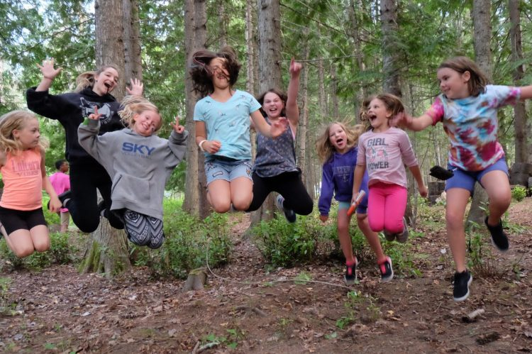 6 campers jumping in the air