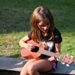 Faith learning how to play the ukulele at the campfire.