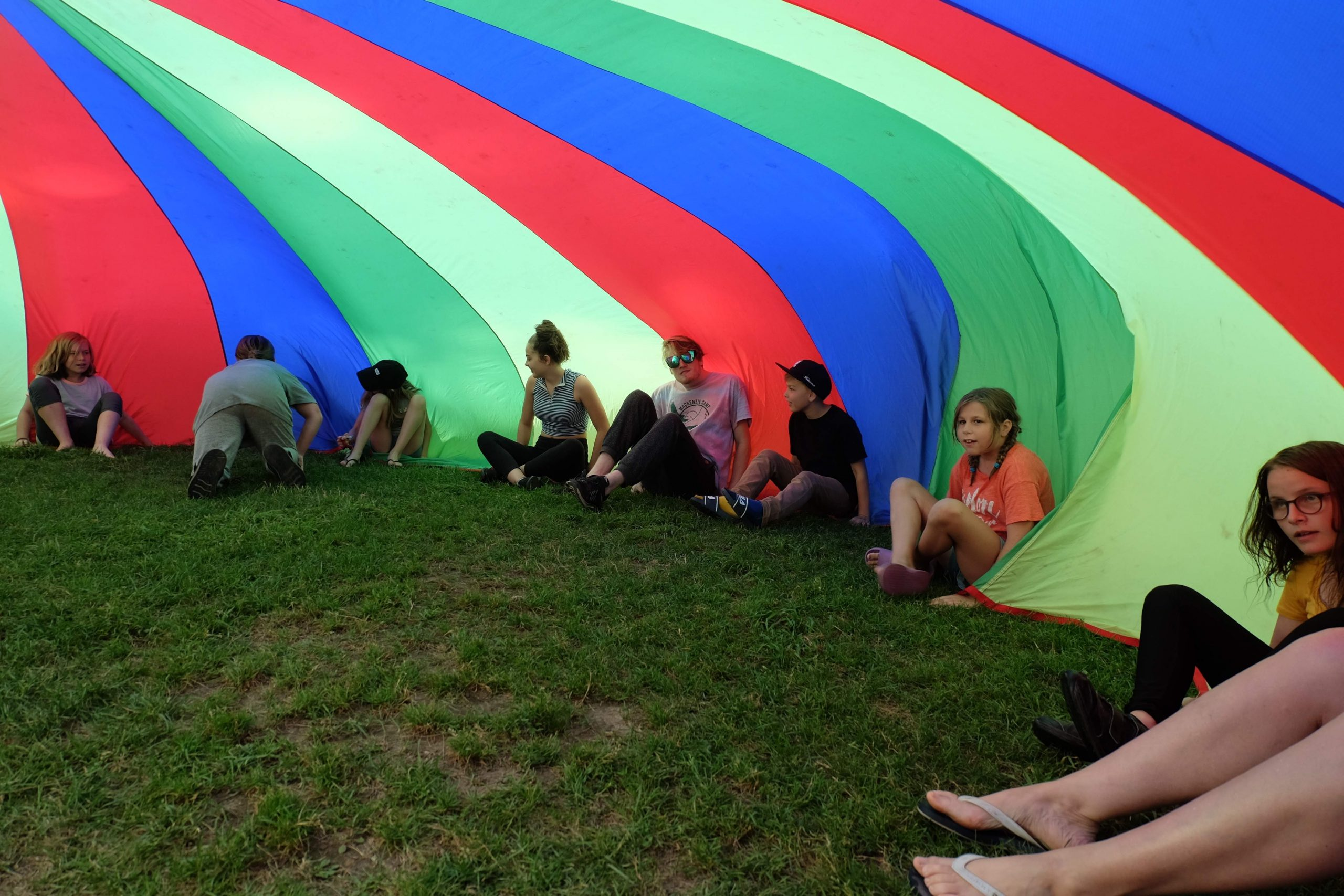 campers playing under the rainbow parachute