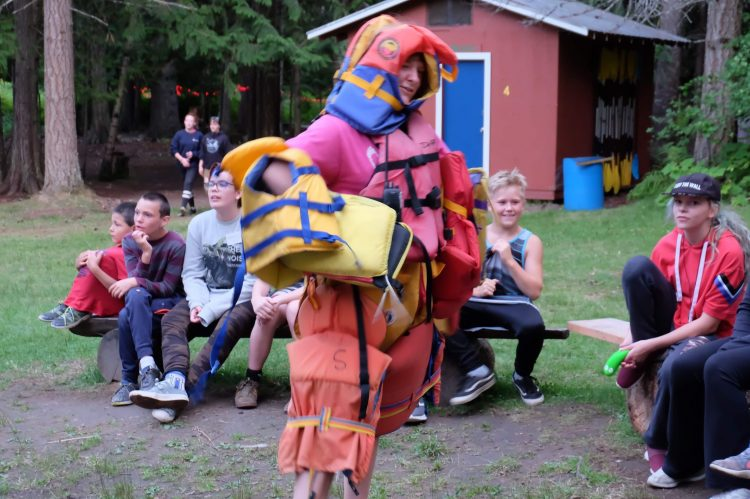 A counsellor dressed up in lots of lifejackets from the wide game, leading a campfire song.
